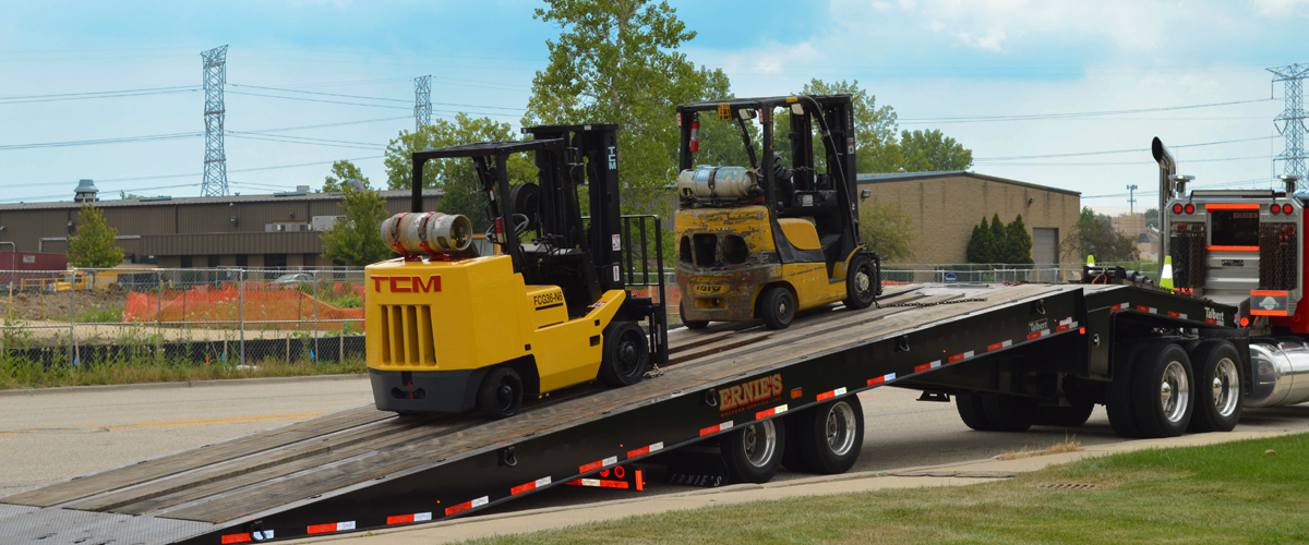 Large trailer carrying forklifts that need a used forklift price from Advantage Material Handling.