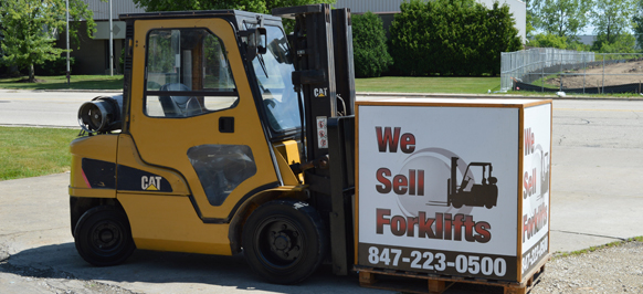 One of the used forklifts for sale holding a sell forklifts sign.